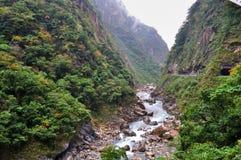Río con las rocas en los pies de montañas Fotos de archivo