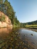 Río con reflexiones en acantilados del agua y de la piedra arenisca Fotos de archivo libres de regalías