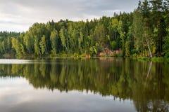 Río con reflexiones en acantilados del agua y de la piedra arenisca Imagen de archivo libre de regalías