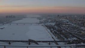 Río congelado enorme en invierno con la ciudad grande nevada en ambos lados en puesta del sol almacen de metraje de vídeo