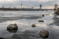 Río congelado, piedras que mienten en el hielo y altos edificios en el fondo Imagen de archivo