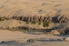 Río de Kunene delante de las dunas de arena antiguas elevadas del desierto de Namib de Namibia y de Angola fotografía de archivo libre de regalías