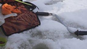 Río de la caña de pescar en invierno en el hielo cerca del agujero Río de la caña de pescar en invierno en el hielo