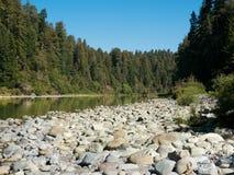 Río de la montaña con las piedras redondas en su banco Fotos de archivo