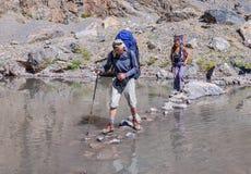 Río de la montaña de la travesía del hombre y de la mujer Imagenes de archivo