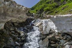 Río de la montaña debajo de la nieve del verano en montañas cárpatas Fotografía de archivo