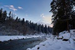 Río de la montaña del invierno con nieve y agua verde en la puesta del sol Río de Bolshoy Zelenchuk Rusia imagenes de archivo