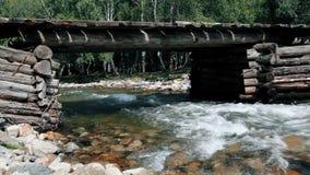 Río de la montaña que fluye debajo de un puente de madera escénico Un río con una parte inferior de piedra Curso rápido de un río metrajes