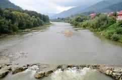 Río de la montaña rocosa en el fondo de las casas y del cielo de las montañas fotografía de archivo