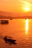 Río de la salida del sol de la silueta del barco. Fotos de archivo