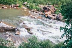 Río de las montañas con los rápidos y las costas rocosas Foto de archivo libre de regalías