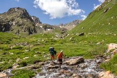 Río de las montañas de la travesía con la mochila foto de archivo