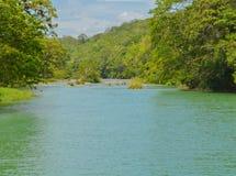 Río de Macal que fluye debajo de la reserva arqueológica de Xunantunich Las ruinas mayas antiguas fuera de San Ignacio, Belice fotos de archivo