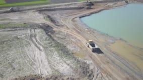 Río de Vislock, Polonia - pueden 2, 2018: Un camión volquete se carga con el suelo La tierra trabaja en la mina de la grava del r almacen de video