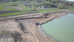 Río de Vislock, Polonia - pueden 2, 2018: Un camión volquete se carga con el suelo La tierra trabaja en la mina de la grava del r metrajes