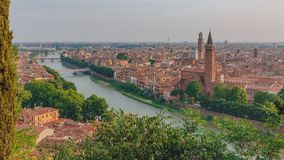 Río del Adigio por el centro histórico de Verona, Italia, con el campanario de la iglesia de Santa Anastasia y de la torre de Lam imagen de archivo libre de regalías