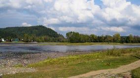 Río del paisaje del verano y Mountain View en el fondo del cielo metrajes