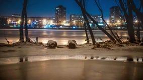 Río desbloqueado en invierno, en el banco del hielo, siluetas de árboles En el fondo las luces de la ciudad de la noche almacen de metraje de vídeo