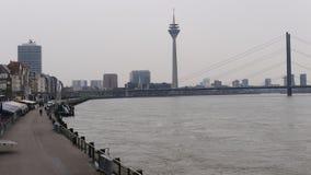 Río el Rin en Düsseldorf Alemania, vista a la 'promenade' de la orilla, en el puente y la torre de Oberkasseler del fondo foto de archivo libre de regalías