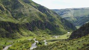 Río entre las montañas cubiertas con la vegetación almacen de video