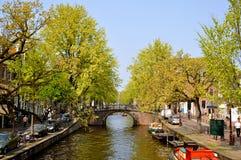 Río hermoso con los barcos y el puente en Amsterdam Imagen de archivo