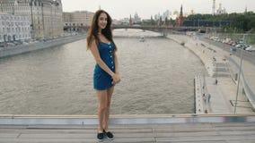 Río modelo del puente del soporte de la mujer morena que mira la cámara y la sonrisa dulce 4k almacen de video