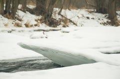 Río parcialmente congelado con un pedazo de hielo que resalta Imágenes de archivo libres de regalías