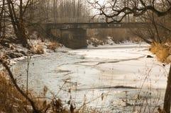 Río parcialmente congelado con un puente Fotografía de archivo libre de regalías