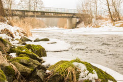 Río parcialmente congelado con un puente Imagen de archivo libre de regalías