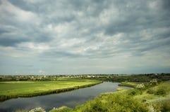 Río que atraviesa el campo antes de lluvia Foto de archivo libre de regalías