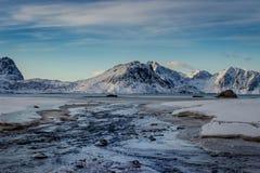 Río que fluye abajo a la playa de Haukland en las islas de Lofoten en invierno fotografía de archivo libre de regalías