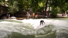 Río que practica surf en el jardín inglés del ` s de Munich, Alemania