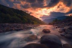 Río rápido de la montaña que fluye en tiempo de la puesta del sol imagenes de archivo