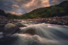 Río rápido de la montaña que fluye en tiempo de la puesta del sol Fotos de archivo libres de regalías