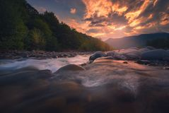 Río rápido de la montaña que fluye en tiempo de la puesta del sol Imagen de archivo libre de regalías