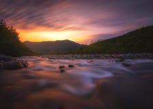 Río rápido de la montaña que fluye en tiempo de la puesta del sol Imagen de archivo