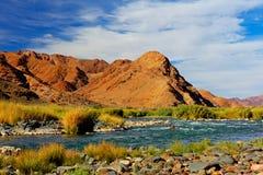Río rojizo de las montañas y cielo azul Imágenes de archivo libres de regalías