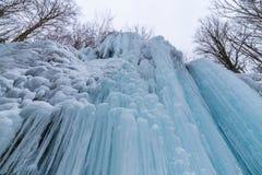 Río salvaje, cascadas congeladas hermosas y nieve fresca en un bosque de la montaña, en un día de invierno frío imagenes de archivo
