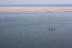 Río santo de Ganga con un bote pequeño en Varanasi Fotografía de archivo
