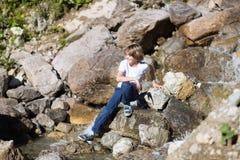 Río siguiente sonriente del adolescente pequeño en montañas Fotografía de archivo