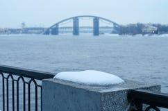 Río urbano con un puente inacabado del arco en invierno fotografía de archivo