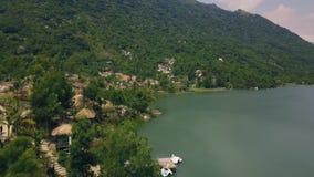 Río y edificio hermosos de la montaña en la opinión aérea de la orilla Camino en lanzamiento verde del abejón de la montaña Opini almacen de metraje de vídeo