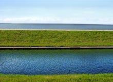 Río y mar paralelamente a hierba verde Foto de archivo