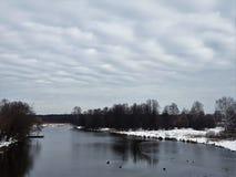 Río y nieve en los bancos con los árboles contra un cielo claro imagenes de archivo
