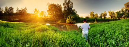 Río y pescador en puesta del sol Fotos de archivo libres de regalías