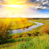 Río y prados verdes por la tarde Imagen de archivo