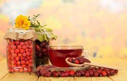 Różanej i filiżanki w szklanych słoju rowan jagodach, dzikiej herbacie obraz stock