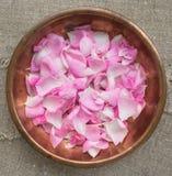 Różani płatki w miedzianym talerzu Zdjęcie Stock