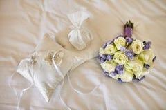 Róże, fiołkowy kwiatu bukiet w pastelu i poduszka dla obrączek ślubnych obrazy royalty free