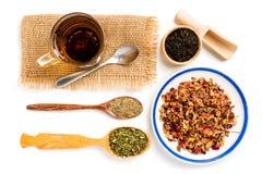 Różna herbata w drewnianych łyżkach, filiżance i spodeczku na białym tle jakby, Obraz Stock